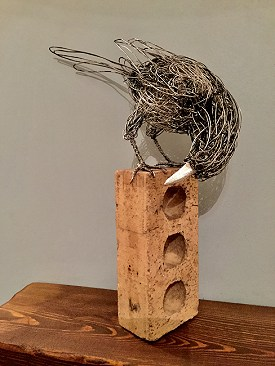 Glimpse - A magpie made using stainless steel wire and a house brick